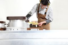 Free Carpenter Man Works With Wooden Planks In The Joinery, Measure With Meter, With Computer Numerical Control Center, Cnc Machine, Stock Photos - 144929683