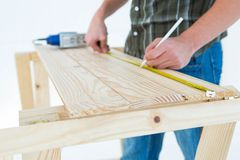 Carpenter marking with measure tape on wooden plank Royalty Free Stock Photos
