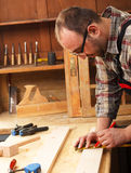 Carpenter marking a measurement on a wooden plank Stock Photos