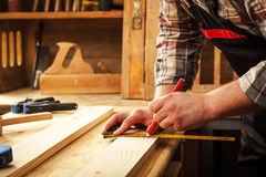 Carpenter marking a measurement on a wooden plank Royalty Free Stock Photography