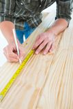 Carpenter marking with tape measure on wooden plank Royalty Free Stock Photos