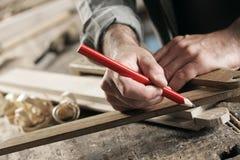 Carpenter Marking a Wooden Plank Stock Photos