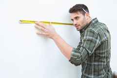 Carpenter measuging white wall with measure tape. Side view of male carpenter measuging white wall with measure tape at home Stock Image