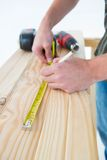 Carpenter with measure tape marking on plank Stock Images