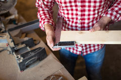 Carpenter measures the board thickness of the corner, joiner's s Royalty Free Stock Photography