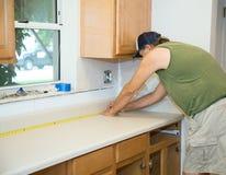 Carpenter Measures Counter Top. Carpenter measuring laminate counter top during kitchen remodel stock photo