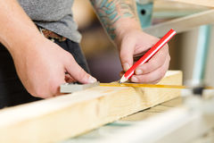 Carpenter measures the length of a wood plank before sawing Royalty Free Stock Photos