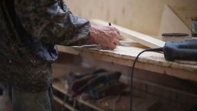 The carpenter measures with a ruler and pencil making marks stock footage