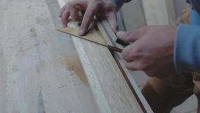 A carpenter measures a wooden board with a square at an angle and marks the dimensions with a pencil. 4k. 4k video. slow motion. 24 fps stock video footage