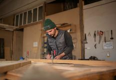Carpenter Measuring A Piece Of Wood in his workshop royalty free stock photos