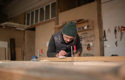 Carpenter Measuring A Piece Of Wood in his workshop royalty free stock image