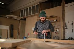 Carpenter Measuring A Piece Of Wood in his workshop stock images