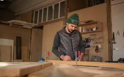 Carpenter Measuring A Piece Of Wood in his royalty free stock images