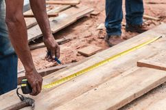 Carpenter measuring the size of a wooden plank for cut. Hands of a carpenter with a measuring tape, measuring the size of a wooden plank to make a mark for royalty free stock image