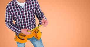 Carpenter with measuring tape against orange background Royalty Free Stock Images