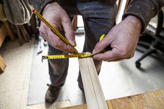 Carpenter measuring wood and marking with pencil Stock Images