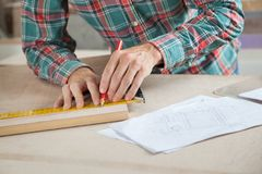 Carpenter Measuring Wood While Marking In Workshop Stock Photography