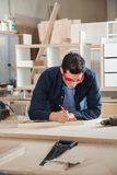 Carpenter Measuring Wood With Ruler And Pencil Royalty Free Stock Photography