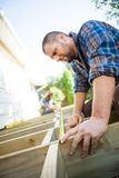 Carpenter Measuring Wood With Tape While Coworker. Mid adult carpenter measuring wood with tape while coworker assisting him at site Royalty Free Stock Photography