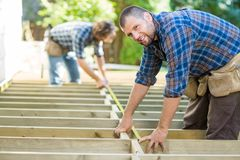 Carpenter Measuring Wood With Tape While Coworker. Portrait of mid adult carpenter measuring wood with tape while coworker assisting him at construction site Royalty Free Stock Photos