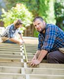 Carpenter Measuring Wood With Tape While Coworker. Portrait of mid adult carpenter measuring wood with tape while coworker helping him at construction site Royalty Free Stock Image