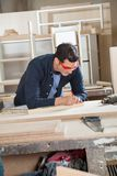 Carpenter Measuring Wood At Workbench Royalty Free Stock Photography