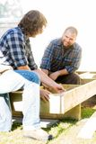 Carpenter Measuring Wooden Frame While Coworker Royalty Free Stock Photo