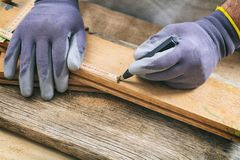 Carpenter measuring with a wooden meter. Man with gloves measuring with a wooden meter Royalty Free Stock Photography
