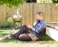 Carpenter Messaging On Cellphone While Leaning On Royalty Free Stock Images
