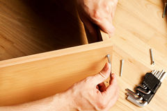 Carpenter mounting wooden furniture Royalty Free Stock Photography