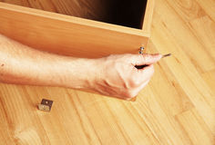 Carpenter mounting wooden furniture Stock Images