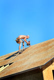Carpenter with Nail Gun. A carpenter working on a roof with a nail gun on top of a house that is under construction Stock Image