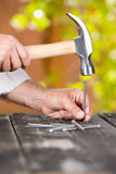 Carpenter nailing a nail. In the home garden Royalty Free Stock Photography