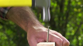 Carpenter nailing a tip with a hammer stock footage