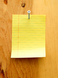 Carpenter Note 4. Blank yellow note paper attached with metal screw on wood background. Construction business note Stock Images