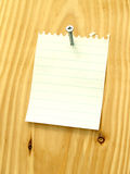 Carpenter Note 5. Blank yellow note paper attached with metal screw on wood background. Construction business note Stock Image