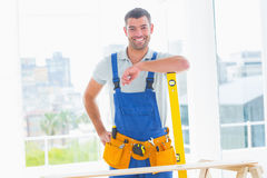 Carpenter in overalls with spirit level in office Royalty Free Stock Image