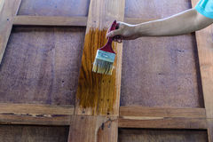 The carpenter is painted beautiful wood doors. Royalty Free Stock Images