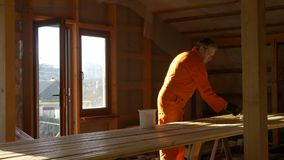 The carpenter painter processes the wood material for floor. Impregnation and imbibition of arranged wooden bars with a brush. Construction and painting works stock footage