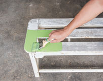 Carpenter painting green color to white wooden bench Stock Photo