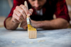 Carpenter painting a piece of wood Royalty Free Stock Photos