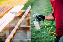 carpenter painting timber with spraygun, outdoors royalty free stock photos