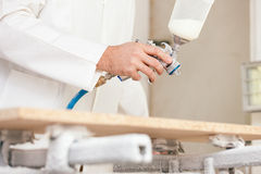 Carpenter painting wood with airbrush royalty free stock photo