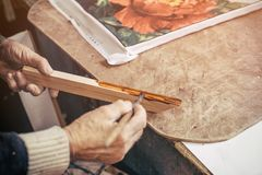 The carpenter paints a wooden blank to make a frame in his bague. Tte workshop. Processing in vintage style Stock Images