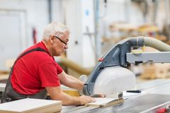 Carpenter with panel saw and fibreboard at factory. Production, manufacture and woodworking industry concept - carpenter working with sliding panel saw and Royalty Free Stock Image