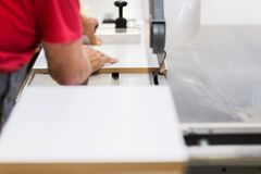 Carpenter with panel saw and fibreboard at factory. Production, manufacture and woodworking industry concept - carpenter working with sliding panel saw and Royalty Free Stock Photos