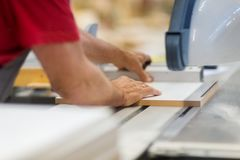 Carpenter with panel saw and fibreboard at factory. Production, manufacture and woodworking industry concept - carpenter working with sliding panel saw and Royalty Free Stock Images