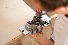 Carpenter placing a jig and piercing Stock Images