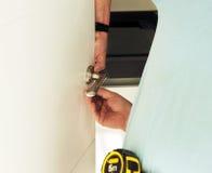 Carpenter placing a new door handle Stock Photography