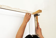 Carpenter placing a new door in the reform of the house Stock Photos